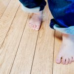 家の床を歩く子供の足
