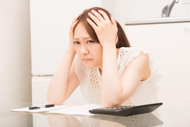 キッチンの収納に悩み頭を抱える女性